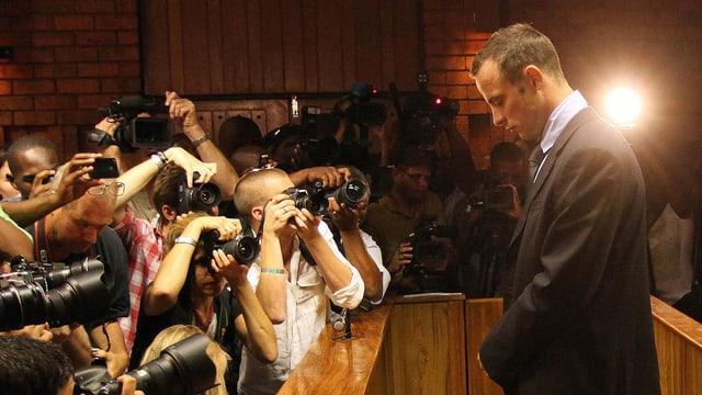 Oscar Pistorius mit gesenktem Kopf, vor ihm Dutzende Journalisten