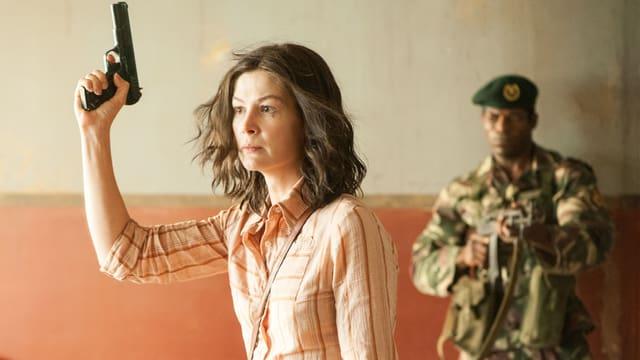 Rosamund Pike mit Pistole in ihrer Rolle als deutsche Terroristin Brigitte Kuhlmann.