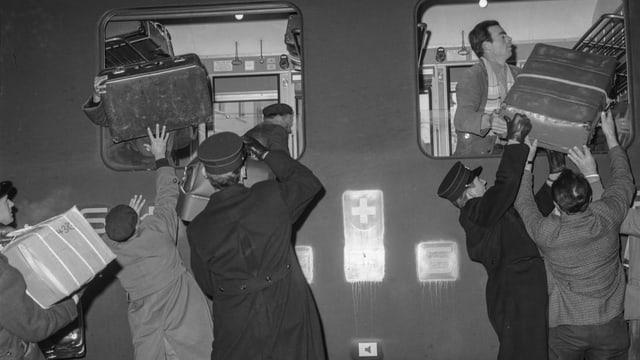 Italienische Gastarbeiter laden ihre Koffer in einen Zug.