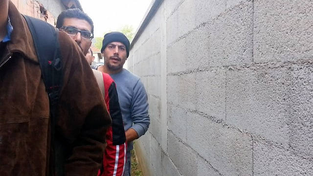 3 Männer hinter einem Haus laufen einer Wand entlang.