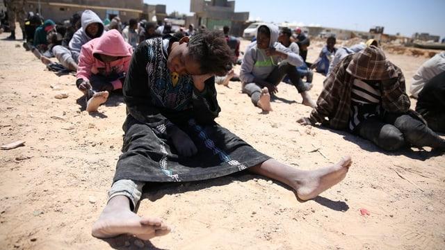 Erschöpfte Flüchtlinge sitzen auf staubigem Boden.
