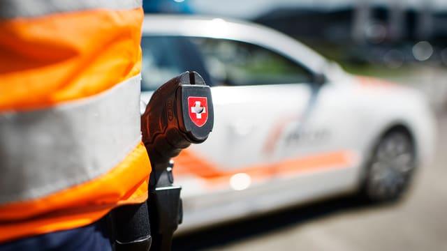 Ein Polizist von Hinten mit einer Waffe auf dem man ein Schweizerkreuz sieht.