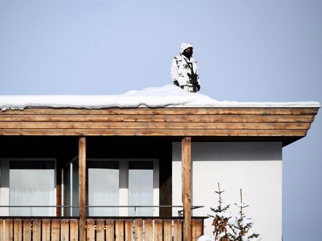 Ein weiss getarnter Polizist auf einem Hausdach.
