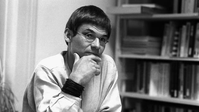 Ein Mann stützt sein Kinn auf seine Hand und sitzt vor einer Bücherwand.