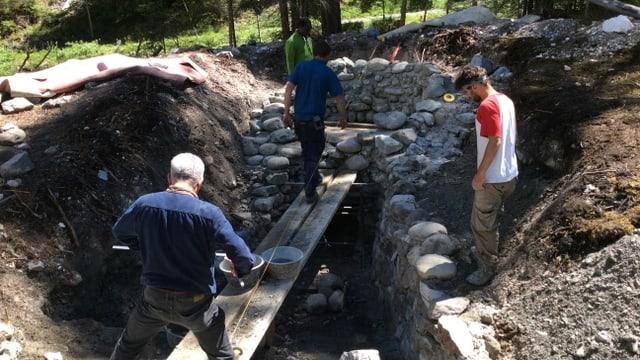 Drei Männer arbeiten an einem Ofen aus Steinen.