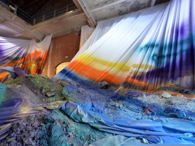 In einem Raum sind riesige weisse Tücher aufgehängt, auf denen Bauschutt liegt. Darauf wurde grossflächig Farbe gesprüht.