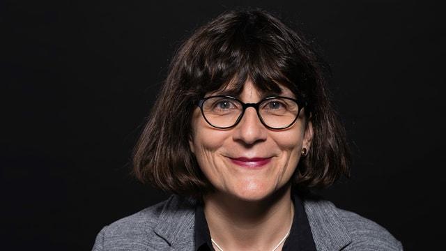 Gesicht von Christa Binswanger mit Brille und schulterlangem, dunkelbraunem Haar.