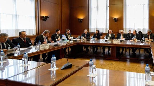 Regierungsvertreter sitzen in einem Sitzungszimmer an einem Tisch.