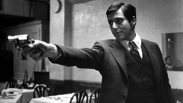 Mann im Anzug hält Waffe in der Hand.
