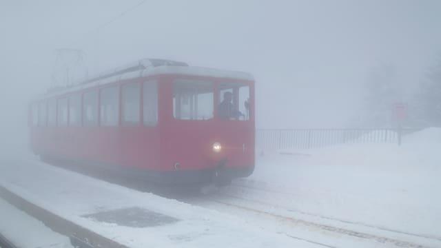 Ein roter Bahnwagen der Rigi Bahnen in dichtem Nebel