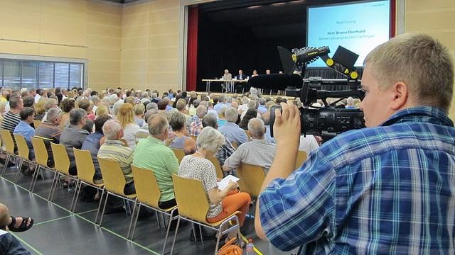 Kameramann filmt in einem Saal, wo es viele Leute hat.