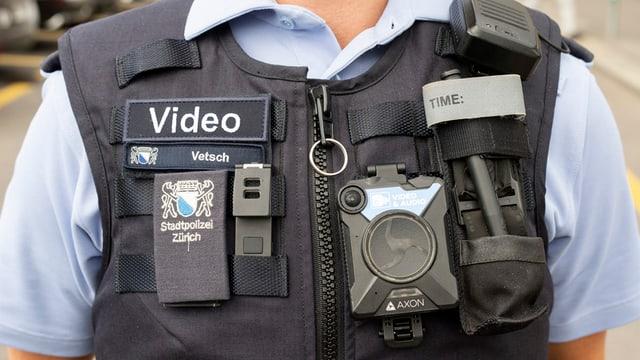 Weste einer Polizistin mit einer Bodycam, Funk und Abzeichen dran