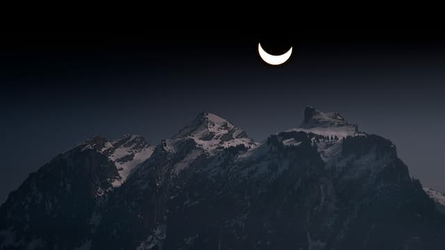 The crescent of the sun looks darkened like the crescent moon.