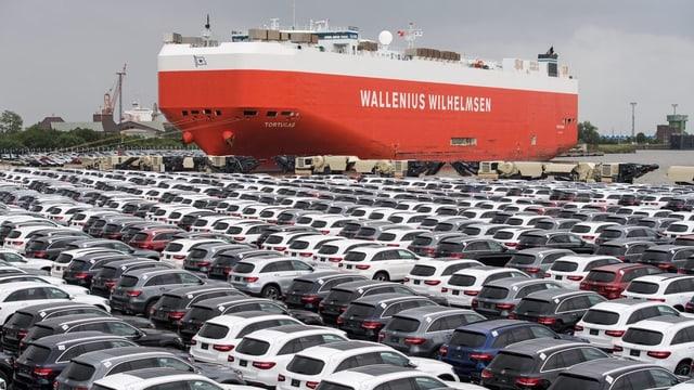 Autos vor einem Frachtschiff.