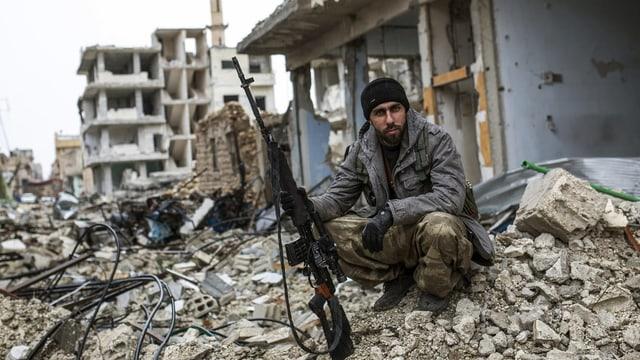Mann mit Gewehr vor zerstörter Stadt.