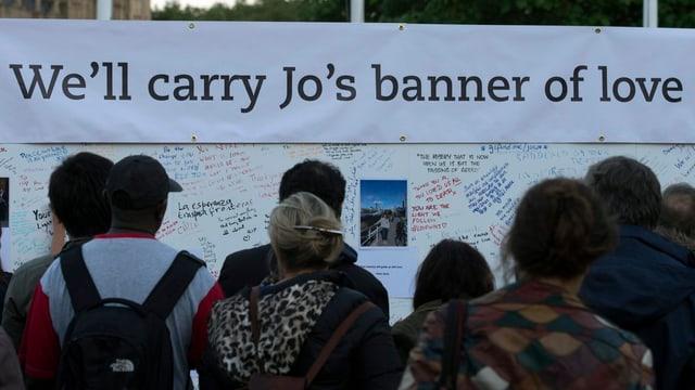 Menschen vor einem Plakat versammelt mit der Aufschrift: «We'll carry Jo's banner of love»
