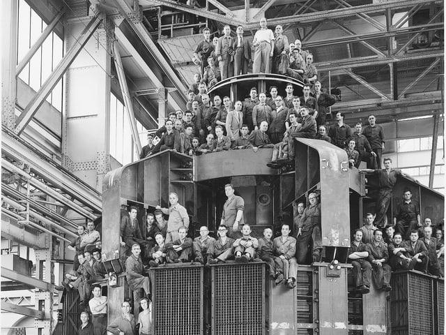 Arbeiter sitzen auf einem haushohen Wasserkraftgenerator