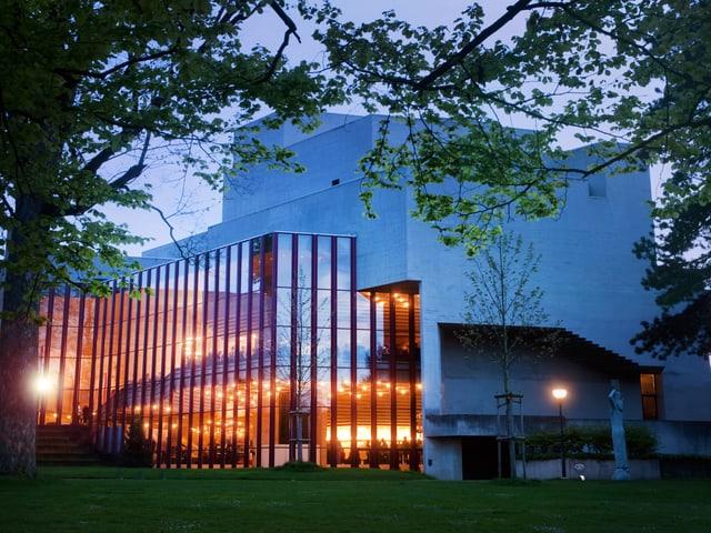 Das Theater St.Gallen in der Dämmerung. Im Foyer brennen Lichter.