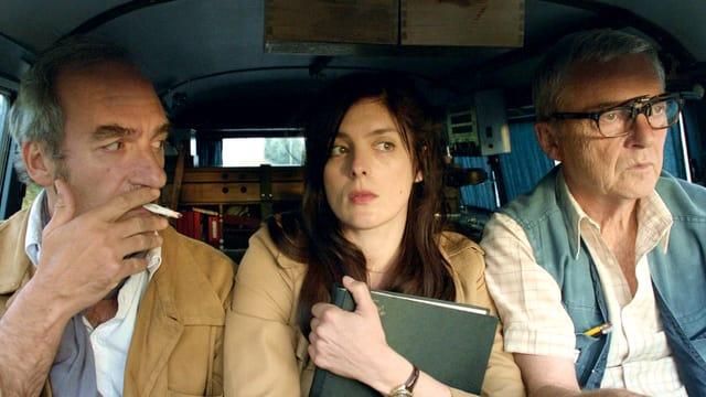 Zwei Männer und eine Frau sitzen in einem Auto.