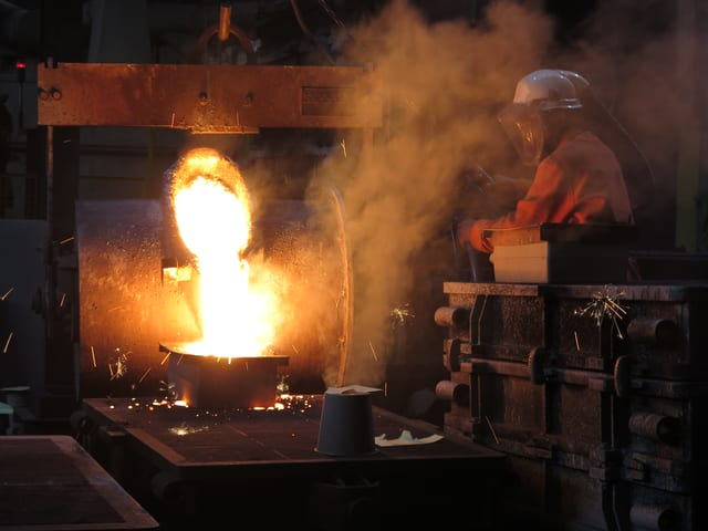 Hell leuchtendes flüssiges Metall wird in eine Form gegossen, ein Mann in Schutzkleidung steht daneben.