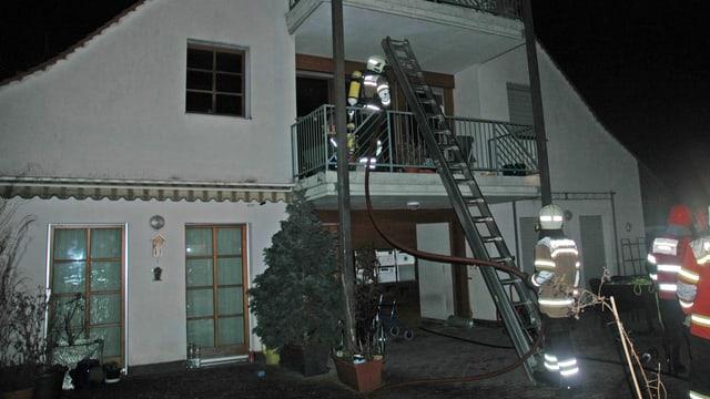 Feuerwehrleute mit Leiter bei Mehrfamilienhaus