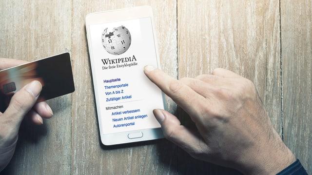Hände mit Kreditkarte und Smartphone. Auf dem Bildschirm ist Wikipedia zu sehen.