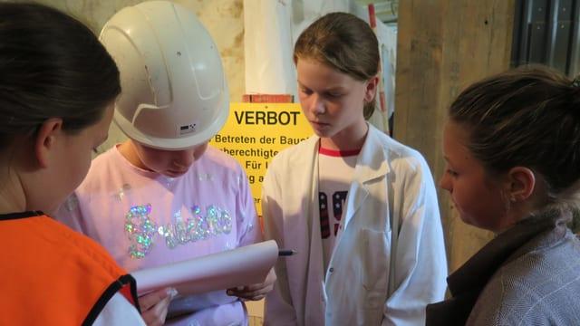 Vier Mädchen schauen auf ein Aufgabenblock. Sie tragen verschiedene Kleider, je nach Rolle. Etwa ein Laborkittel oder Chaquette.
