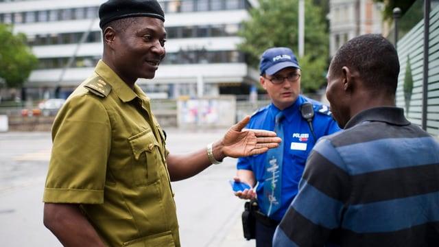 Ein Mann in grüner Polizeiuniform spricht mit einem Afrikaner, beobachtet werden beide von einem Schweizer Polizisten in blauer Uniform.
