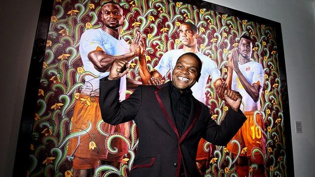 Kehinde Wiley steht vor einem seiner Bilder, das drei schwarze Sportler zeigt. Er lächelt, hat die Arme angewinkelt und die Hände zu fäusten geballt.