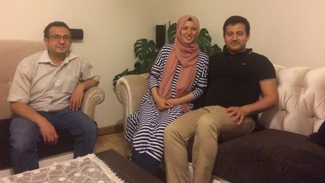 Familie und Gast auf Sofa sitzend