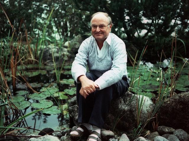 Mann sitzt auf einem Stein vor einem Teich.