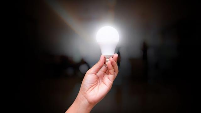 Person hält leuchtende LED-Lampe in der Hand.