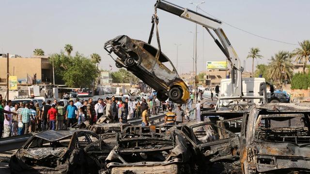 Epizentrum eines Bombenanschlags. Kran birgt zerstörtes Auto.