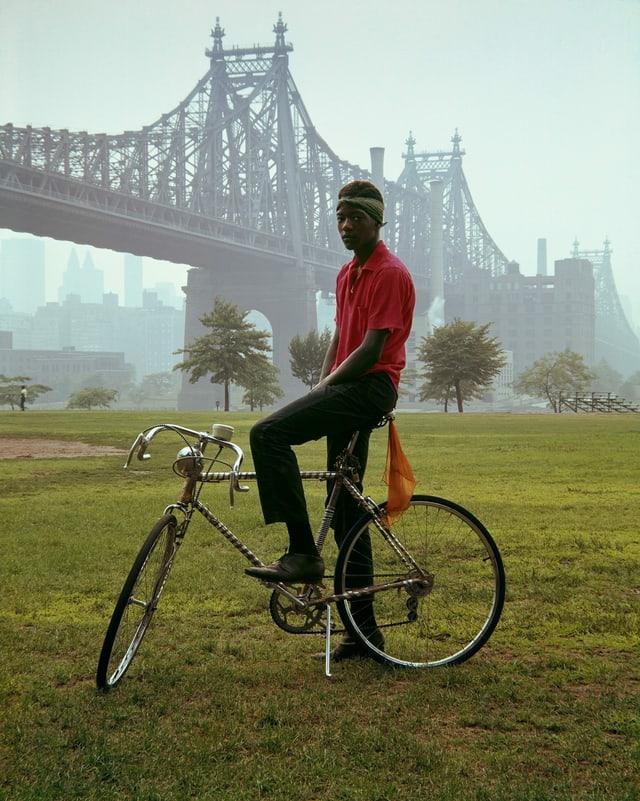 Ein schwarzer Junge posiert auf seinem Rennrad vor der Queensborough Bridge in New York.
