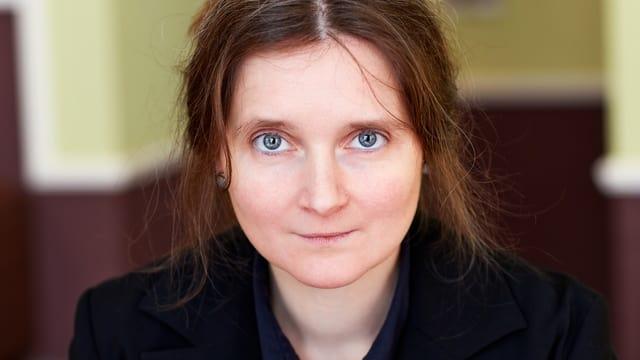 Eine Frau mit blauen Augen und schwarzem Blazer schaut direkt in die Kamera.