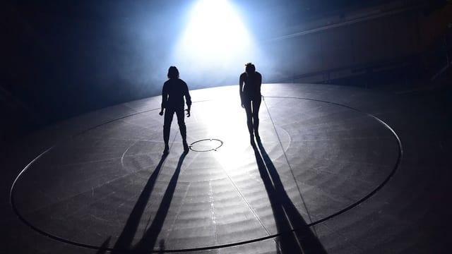 Zwei Menschen auf einer Bühne. Sie werde mit Licht bestrahlt.