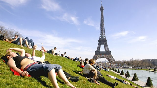 turists giaschan sin ina spunda, en il fund la tur Eiffel a Paris