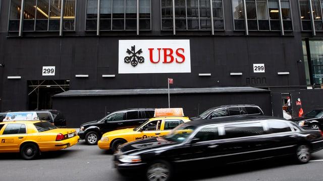 UBS-Firmenschild, davor gelbe Taxis