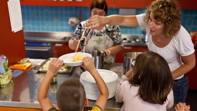 Kinderbetreuerin schöpft Essen in einer Kita-Küche