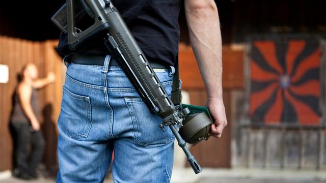 Rückenansicht eines Mannes, quer über den Rücken trägt er ein Sturmgewehr.
