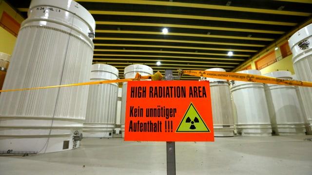 Mehrere Meter hohe, weisse Container für radioaktive Abfälle stehen in einer Lagerhalle, davor ein oranges Schild mit der Warnung «Kein unnötiger Aufenthalt!»
