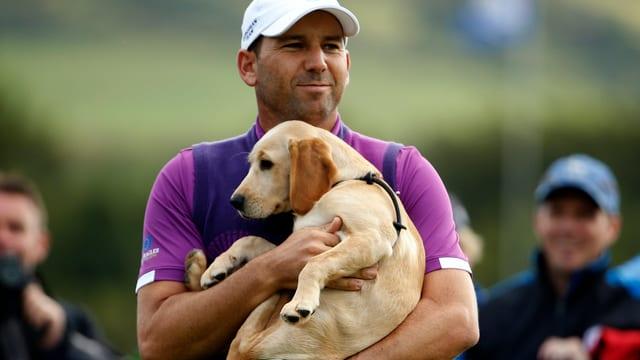 Ein Golfspieler hält einen Hund in den Armen.