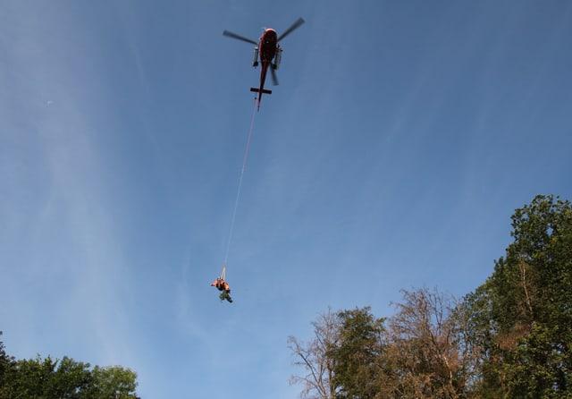 Ein Helikopter fliegt und ein Mann hängt an einem Seil.
