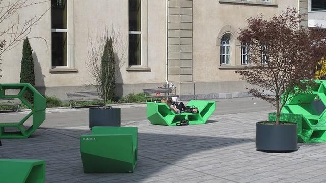 Platz mit grünen Sitzen und Bäumen