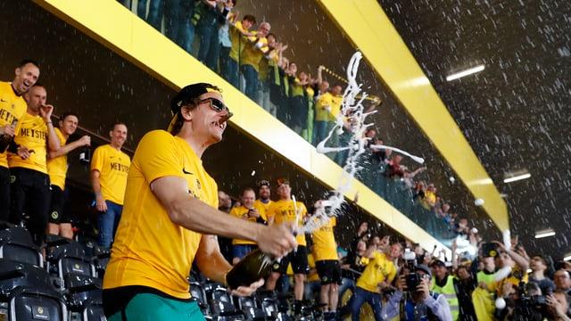 Mann in gelbem T-Shirt verspritzt Champagner auf Zuschauerrängen eines Fussballstadions.
