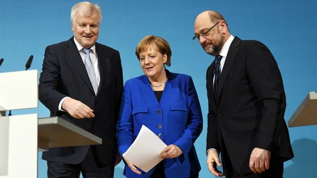Drei Personen in einer Reihe vor einem Rednerpult stehend.