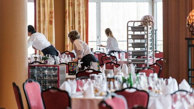 trais emploiads da hotel preparan la sala da mangiar