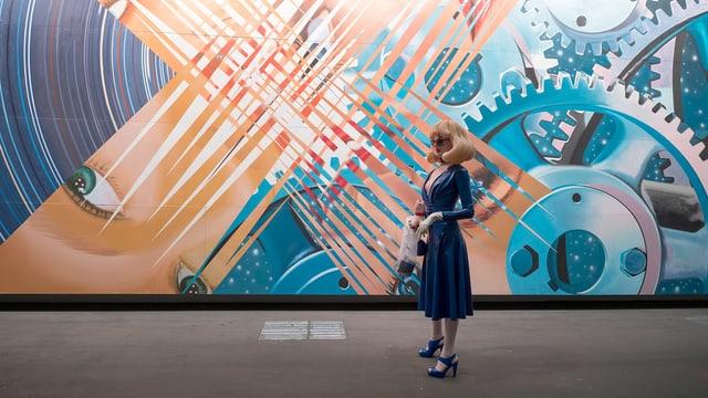 Eine Frau aus Plastik steht vor einer riesigen, collageartigen Malerei.