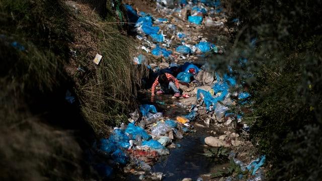 Abfall in einem Bach, ein Kind mitten drin.