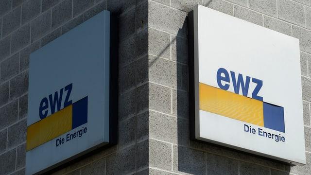 Zwei Firmentafeln des EWZ an einer Hausecke, eine in der Sonne, eine im Schatten